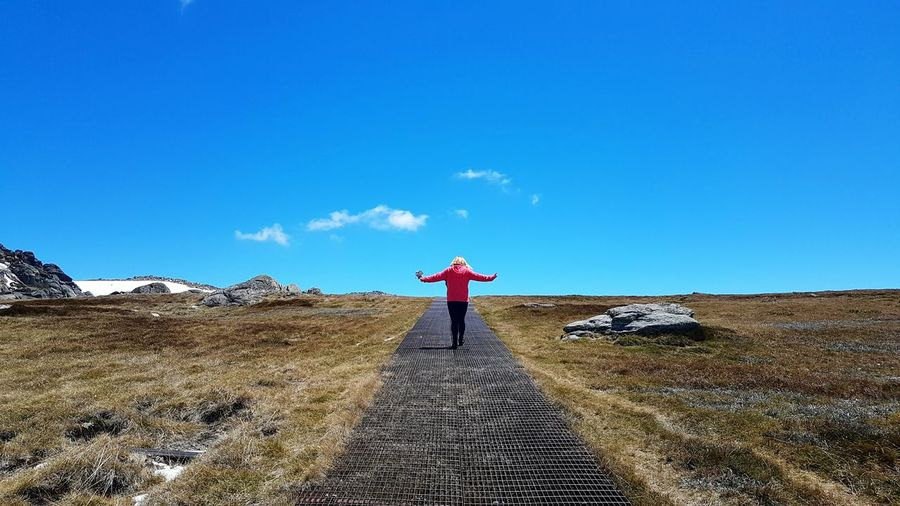 Rear view of woman with arms outstretched standing on field against blue sky during sunny day