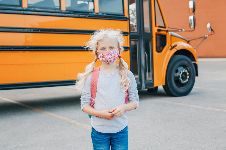 caucasian girl student wearing face mask near yellow bus.  education and back to school. new normal.
