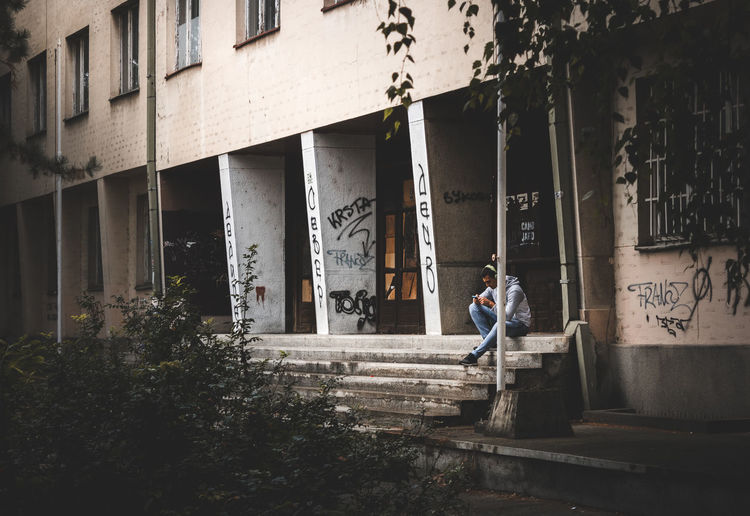 Man standing on staircase of building in city