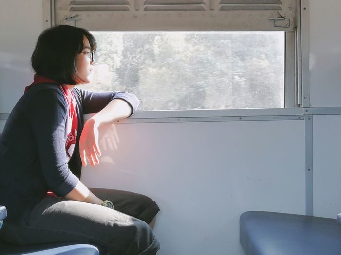 Side view of young woman sitting by window in train