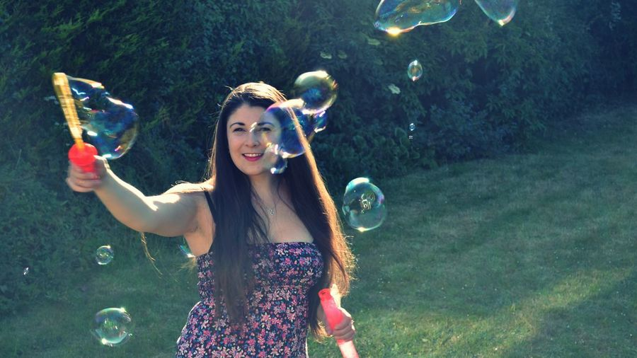 Portrait of young woman blowing soap bubble in parks