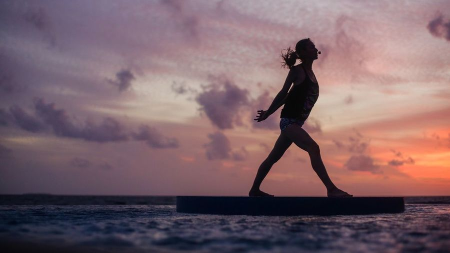 Silhouette Of Woman Practicing Yoga At Sea
