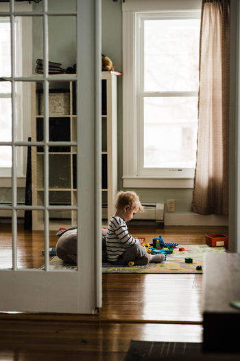 Side view of boy sitting on table at home