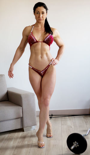 Portrait of muscular woman in bikini standing at home