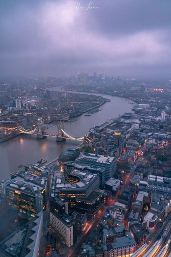 High angle view of illuminated city buildings by river