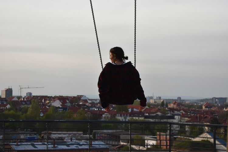 Woman On Swing Against Sky