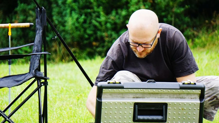 Man looking down by briefcase at grassy field