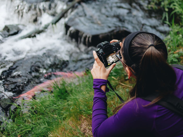 Rear view of woman photographing by stream in forest