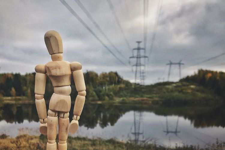 Close-Up Of Wooden Figurine Against Electricity Pylon And Cloudy Sky