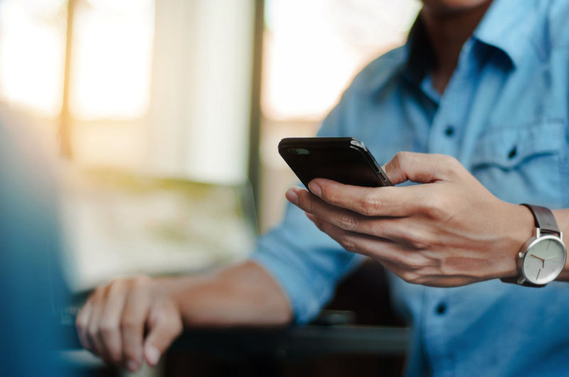 Midsection of man using mobile at table