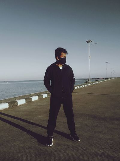 Full length of man wearing mask standing on road against clear sky