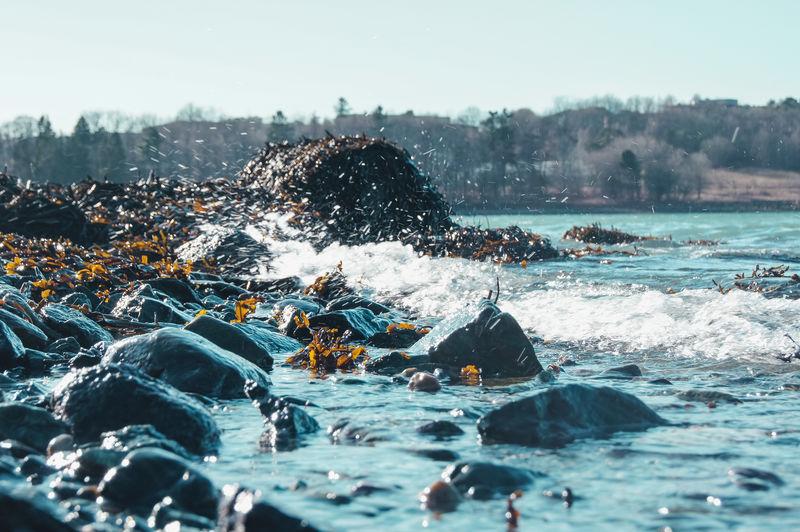Water splashing on rocks against sky