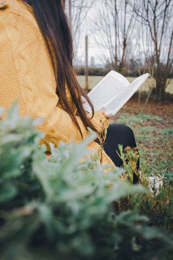 Young woman sitting outdoor and reading a book.