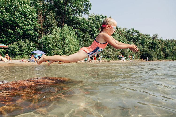 Girl diving in sea against trees