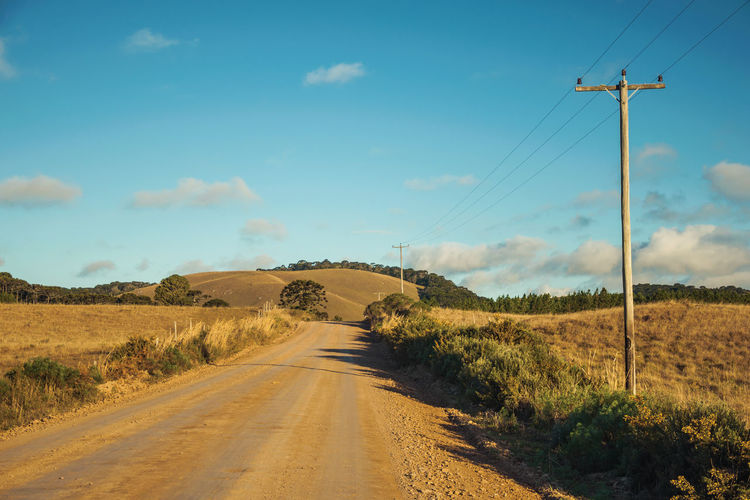 Deserted dirt road passing through rural lowlands with green hills near cambará do sul. brazil.