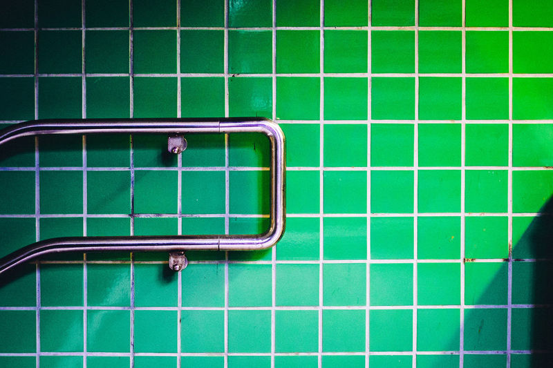 Close-up of metal on green tiled wall