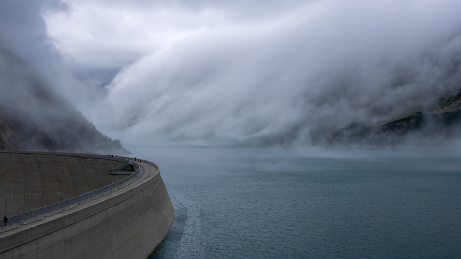Dam by river in foggy weather