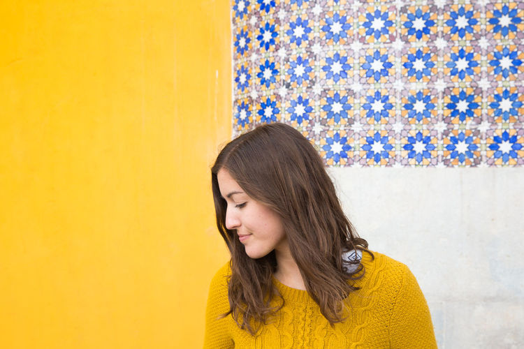 Portrait of a beautiful young woman against yellow wall