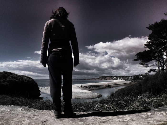 Rear View Of Woman Standing At Shore Against Sky