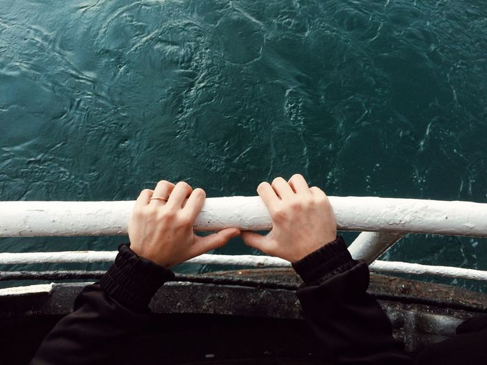 Cropped hand of woman holding railing of nautical vessel on sea