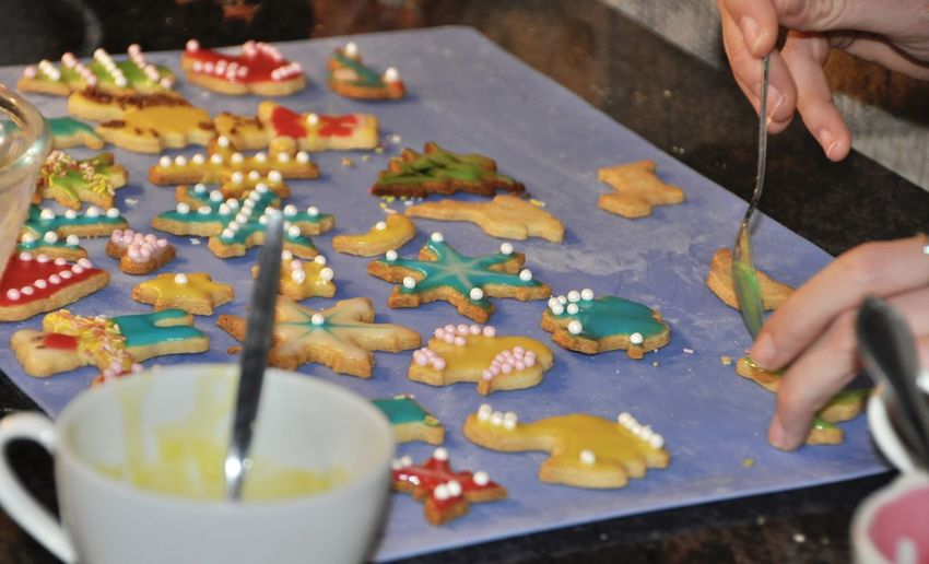 Cropped hand decorating cookies