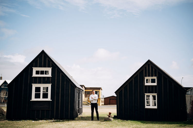 Man standing outside of shed against sky