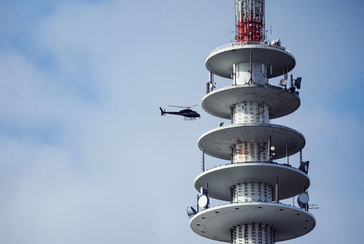 Low angle view of helicopter flying by air traffic control tower by sky