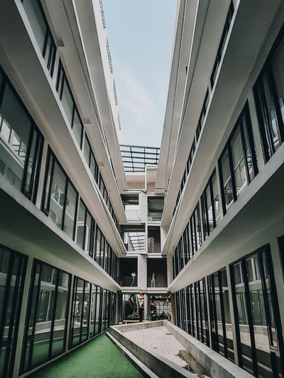 Footpath amidst buildings in city against sky