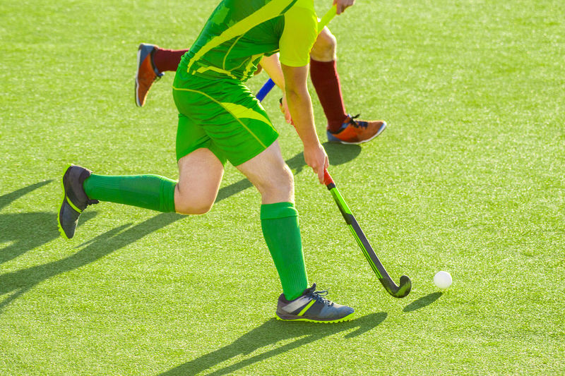 Close up of two field hockey players, challenging eachother for the control and posession of the ball during an intense, competitive match on professional level Field Hockey Fight Grass Green Man Activity Ball Club Day Grass Green Color Leisure Activity Motion Nature One Person Paly Plant Players Playing Shoes Sport Summer Sports