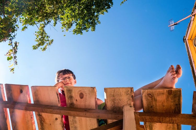 Low angle view of kid lying on  scaffolding against clear sky