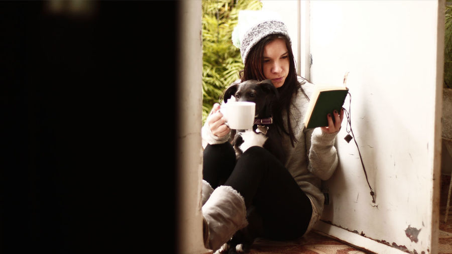 Coffee Coffee - Drink Coffee Cup Cold Cold Days Cold Temperature Day Dog Drink Full Length Girl Girl And Dog Girl Reading Girl Reading A Book Holding One Person One Young Woman Only Sitting Tea Winter Winter Clothes Young Adult Young Women