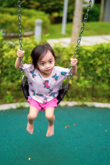 Cute girl on swing at playground
