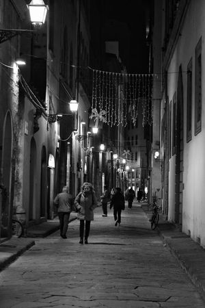 Florence Street By Night Night Illuminated Architecture Building Exterior Large Group Of People Real People People Outdoors Street Photography Contrast Street Florence Italy Florence The Best City In The World Black And White Monochrome Shadows Shadows & Light Casting A Shadow Full Length Lifestyles Winter City Travel Mystery