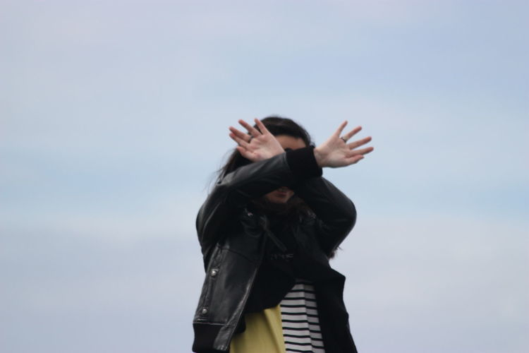 Woman with hands in front of face against clear sky
