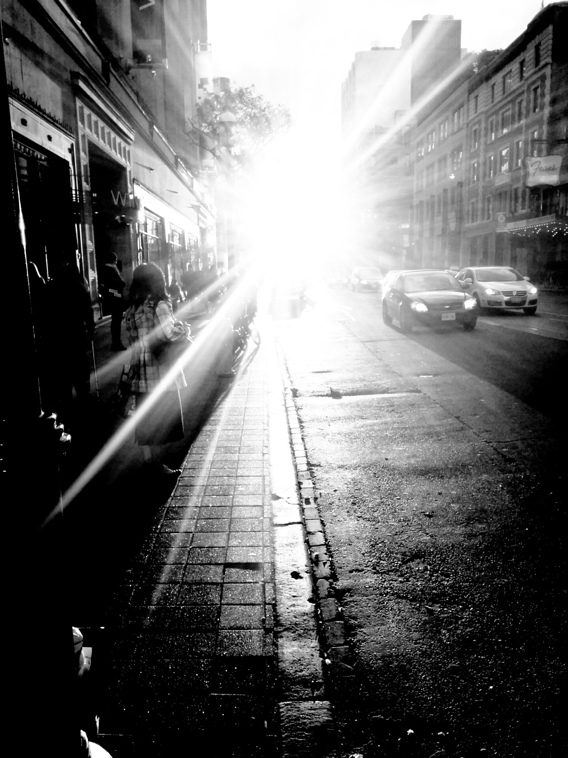 building exterior, transportation, architecture, car, built structure, land vehicle, city, mode of transport, street, sun, city street, sunlight, sunbeam, city life, lens flare, road, incidental people, building, road marking, traffic