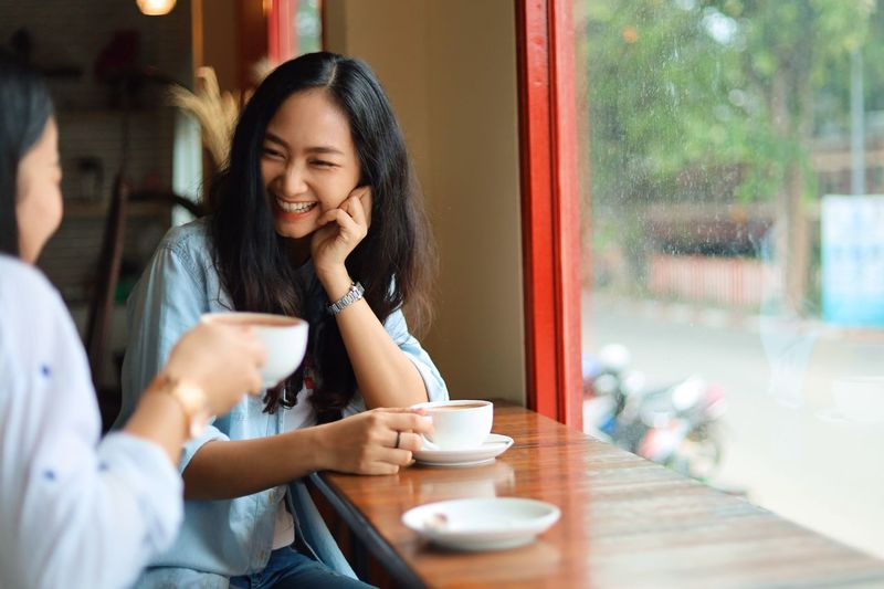 Cup Mug Coffee Cup Drink Food And Drink Cafe Women Young Adult Coffee - Drink Two People Young Women Adult Coffee Table Smiling Lifestyles Sitting Communication Real People Casual Clothing Wireless Technology Outdoors Hot Drink