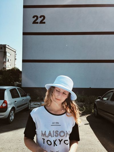 Woman wearing hat while standing against building