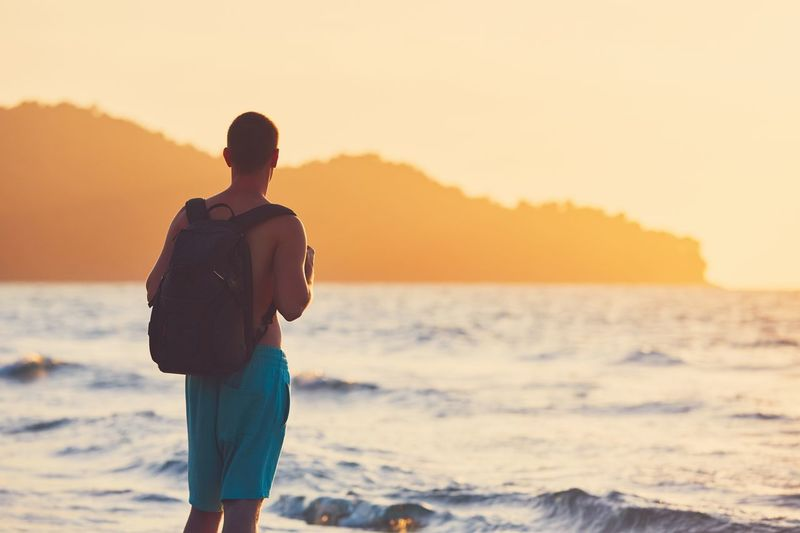 Young traveler with backpack watching amazing sunset. Vacation on the tropical beach. Backpacker Beach Coastline Enjoying Life Golden Hour Landscape Man Moody Sky Nature Nature People Real People Relaxation Scenics Sea Shore Summer Sunset Tourist Travel Travel Destinations Traveler Tropical Climate Vacations Wave