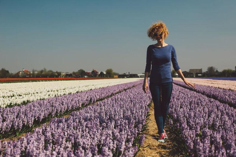 Woman Walking In Flower Field Against Clear Sky