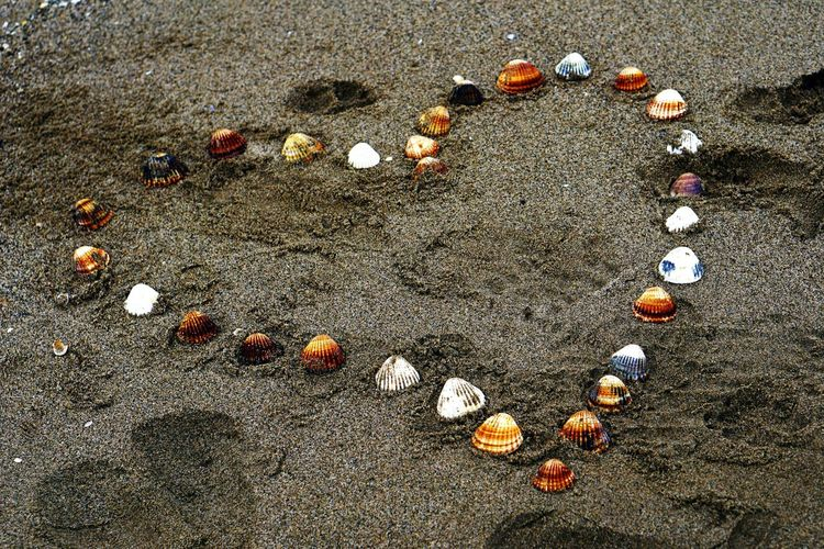 Close-up of sand on beach with a drawing of a heart made of shells