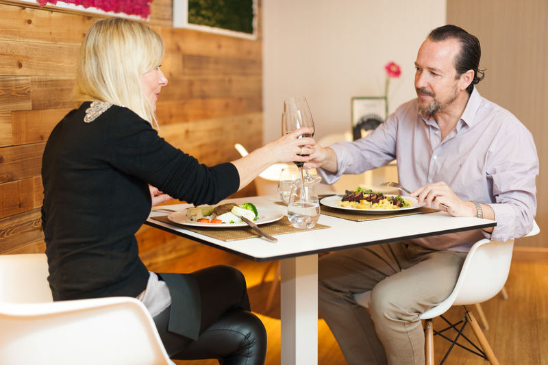 Mature couple toasting wine while sitting at restaurant