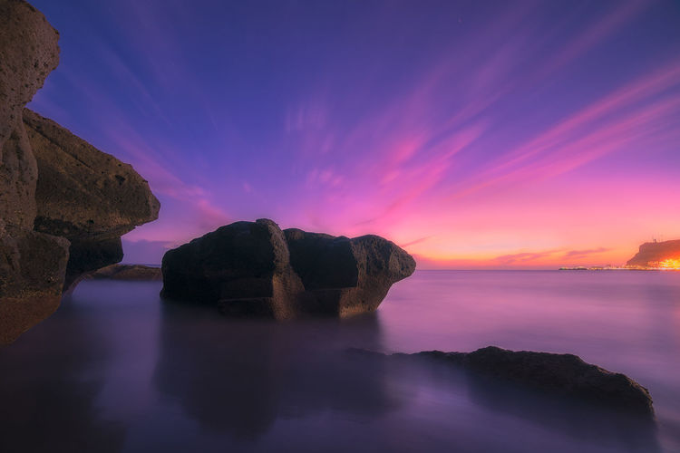 Water Sunset Cloud - Sky Beauty In Nature Rock Scenics - Nature Sky Tranquility Solid Tranquil Scene Rock - Object Sea Idyllic Nature Rock Formation No People Long Exposure Waterfront Non-urban Scene Horizon Over Water Purple Magic
