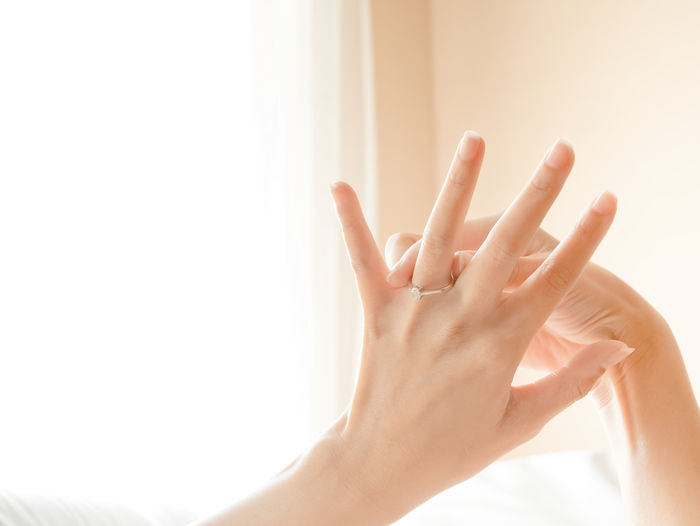 Close-Up Of Woman Hand Wearing Ring At Home