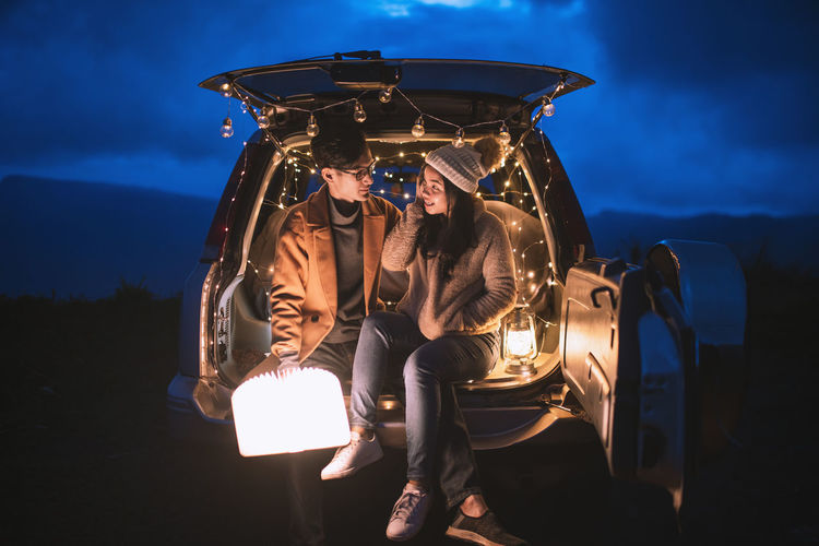 Young couple sitting in illuminated car trunk at night