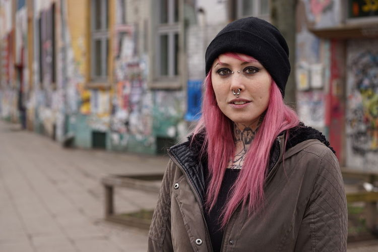 Portrait Of Young Woman With Pink Hair Standing On Street