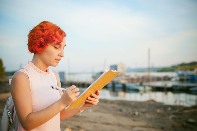 Mid adult woman writing while standing at riverbank against sky during sunset