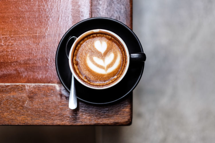 Cafe latte at the edge of a wooden table Coffee - Drink Food And Drink Coffee Cup Coffee Refreshment Drink Frothy Drink Mug Cup Table Crockery Still Life Saucer Eating Utensil Spoon Freshness Indoors  Hot Drink Kitchen Utensil Froth Art No People Latte Non-alcoholic Beverage Froth