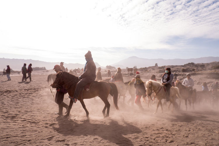 People riding horses on sand against sky