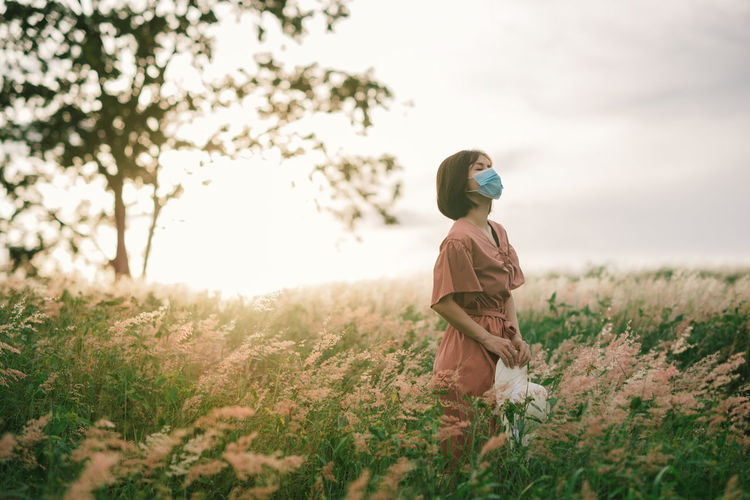 Girl on a spring meadow at sunset.  wears a dress and wide-brimmed hat. breathing through the mask.