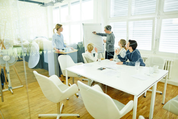 Businessman Explaining Graph To Colleagues In Office During Meeting